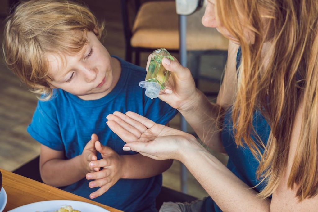 madre colocando antibacterial a su hijo